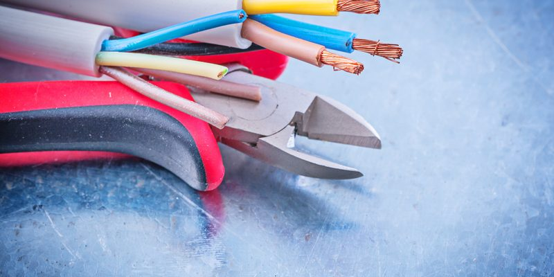 Electrical cables wires cutting pliers on metallic background